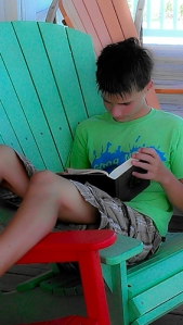 See! A boy is reading in this candid photo.